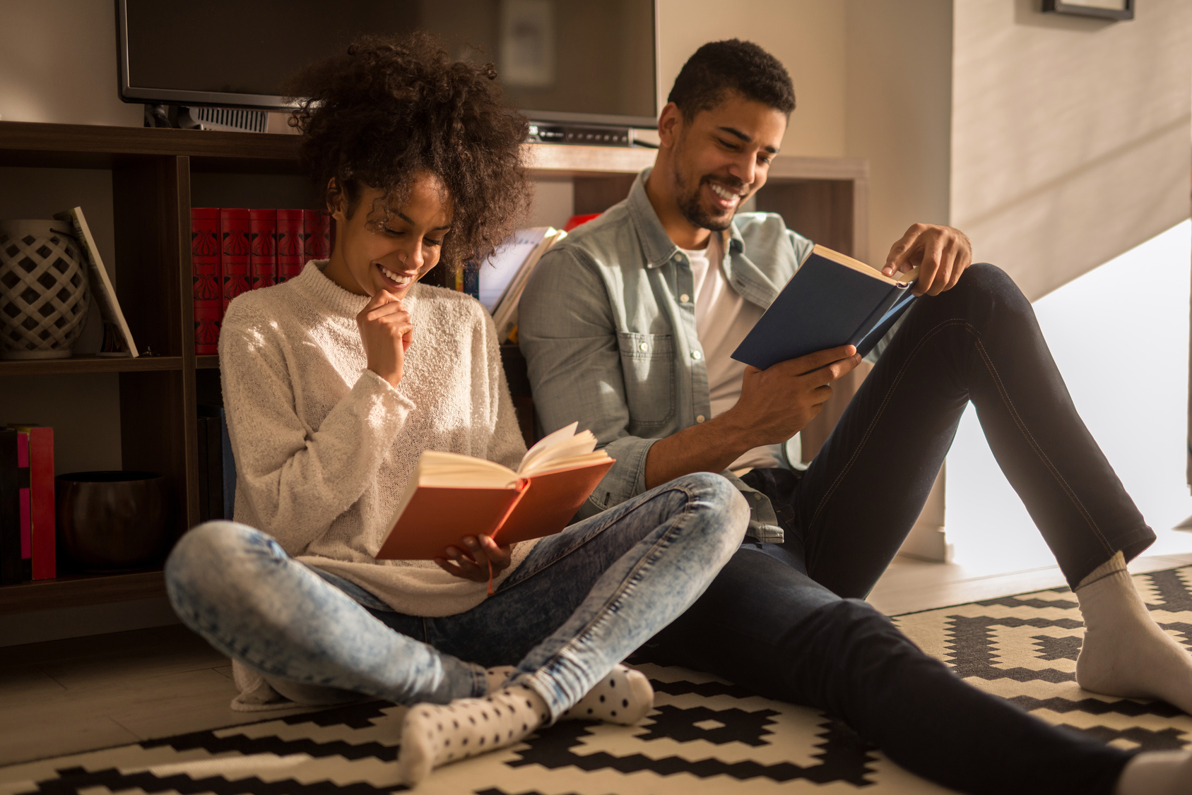 African american couple enjoying reading together at home.